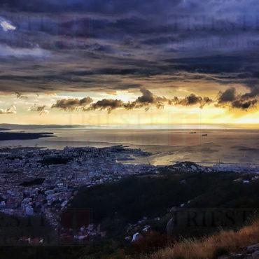 Una panoramica di Trieste dall'alto, con un tramonto che squarcia le nuvole blu